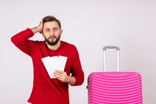 Front view young male with pink bag and holding tickets on white wall voyage flight color trip vacation photo emotion