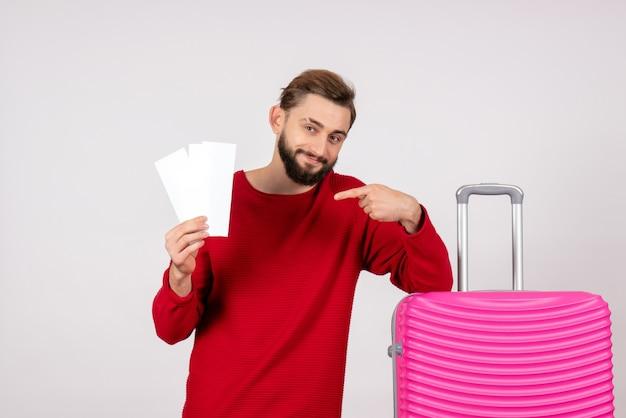 Giovane maschio di vista frontale con la borsa rosa e che tiene i biglietti sulla foto di vacanza di viaggio di colore di volo di viaggio della parete bianca