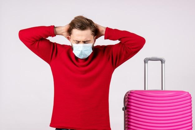 Вид спереди молодой самец с розовой сумкой в маске на белой стене путешествие covid - полет поездка отпуск эмоция вирус цвет