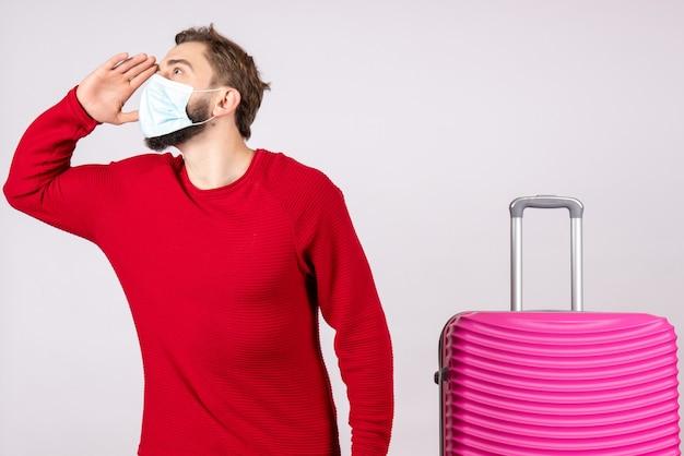 Вид спереди молодой самец с розовой сумкой в маске на белой стене путешествие covid-рейс поездка отпуск эмоции вирус