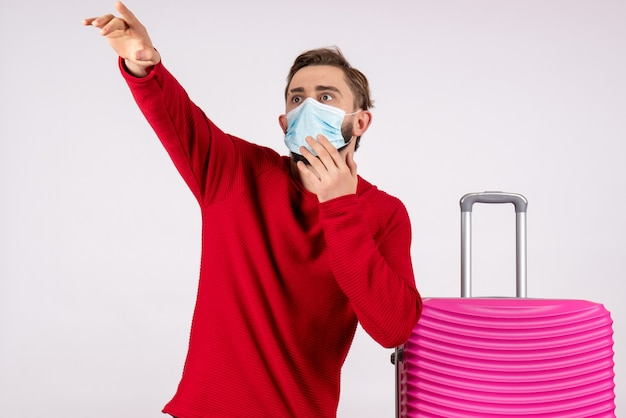 Front view young male with pink bag in mask pointing on white wall voyage covid- flight trip vacation emotion virus