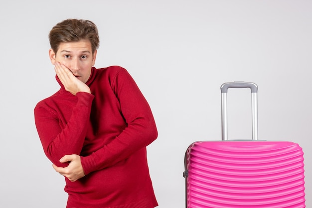 白い背景の上のピンクのバッグと正面図の若い男性