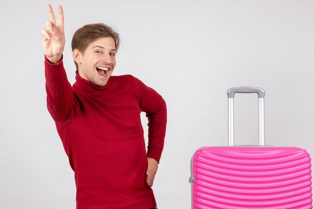 Вид спереди молодой мужчина с розовой сумкой на белом фоне