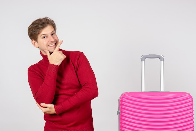 正面図白い背景にポーズをとってピンクのバッグを持つ若い男性