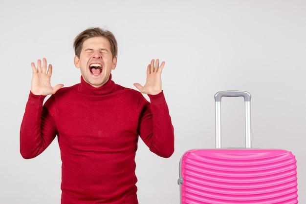 Вид спереди молодой мужчина с розовой сумкой, кричащий на белом фоне, море, отпуск, отпуск, поездка, эмоция, цвет, лето