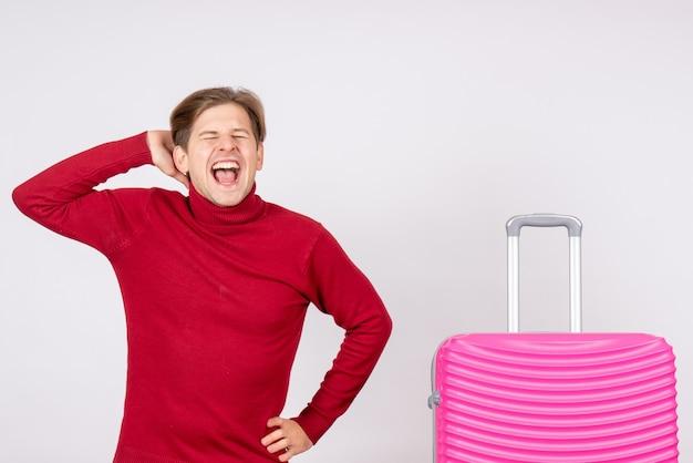 Vista frontale giovane maschio con borsa rosa urlando su uno sfondo bianco emozione modello viaggio volo estate colore vacanza