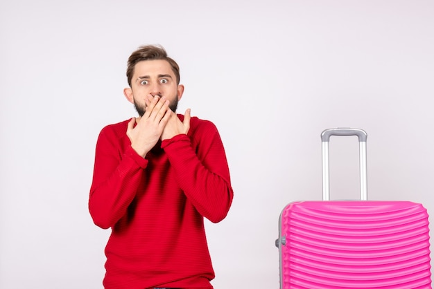 Front view young male with pink bag shocked on white wall trip photo human color vacation flight voyage summer