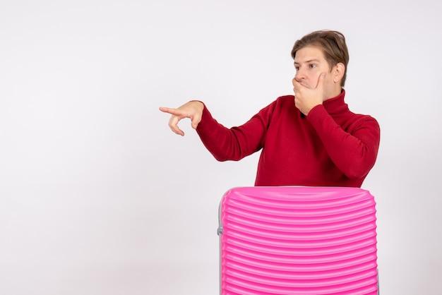 Giovane maschio di vista frontale con la borsa rosa che guarda scioccantemente a qualcosa su fondo bianco