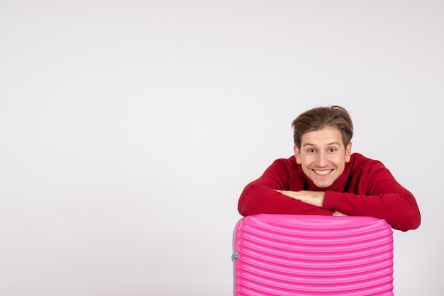 Vista frontale giovane maschio con borsa rosa sorridente su sfondo bianco