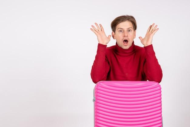 Giovane maschio di vista frontale con il sacchetto rosa sorpreso su priorità bassa bianca