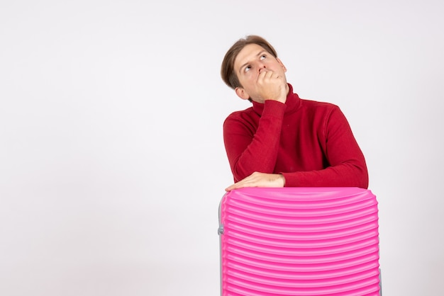 Giovane maschio di vista frontale con il sacchetto rosa che pensa su fondo bianco