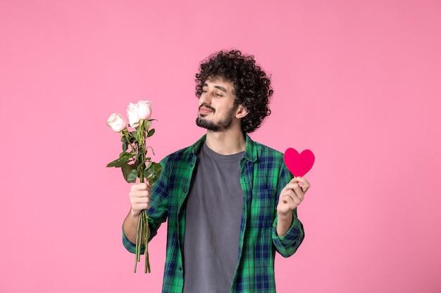 Вид спереди молодой мужчина с розовыми розами и сердечной наклейкой на розовом