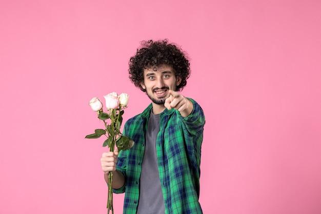 Vista frontale giovane maschio con rose rosa come regalo per la festa della donna in colore rosa