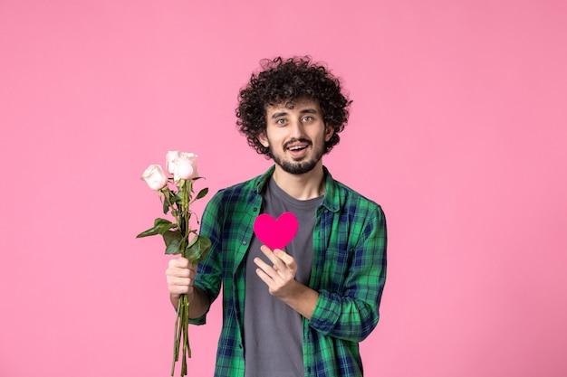 Vista frontale giovane maschio con rose rosa e adesivo cuore su rosa