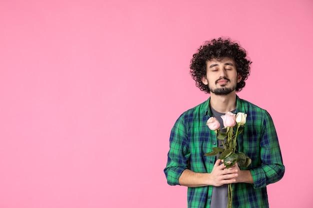 Vista frontale giovane maschio con rose rosa su colore rosa
