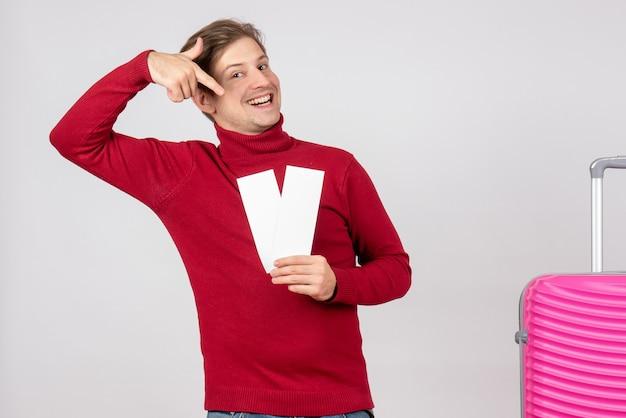 白い背景の上の飛行機のチケットと正面図の若い男性