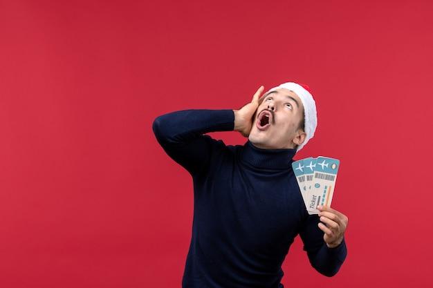 Vista frontale giovane maschio con biglietti aerei spaventato su sfondo rosso