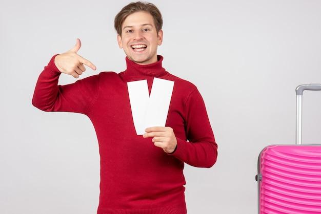 Giovane maschio di vista frontale con i biglietti aerei su priorità bassa bianca