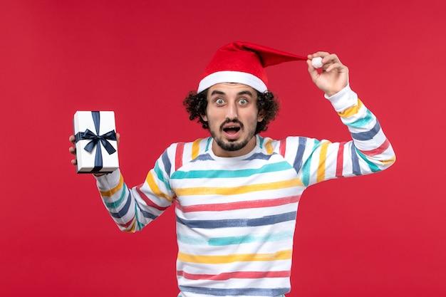 Вид спереди молодого мужчины с настоящим и удивленным лицом на красной стене новогоднего праздника эмоции