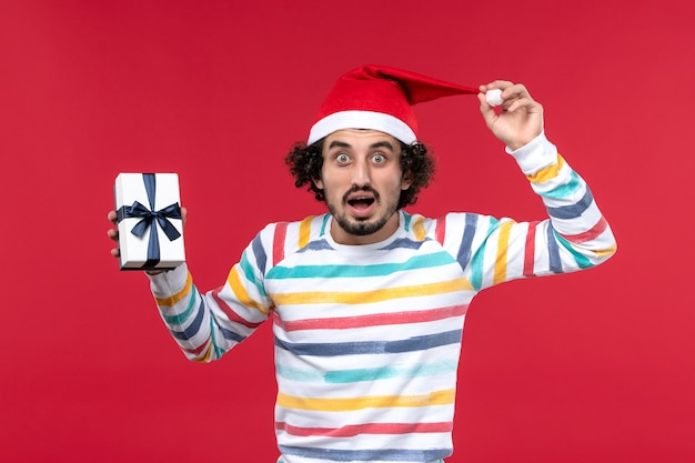 Front view young male with present and surprised face on red wall new year holiday emotion