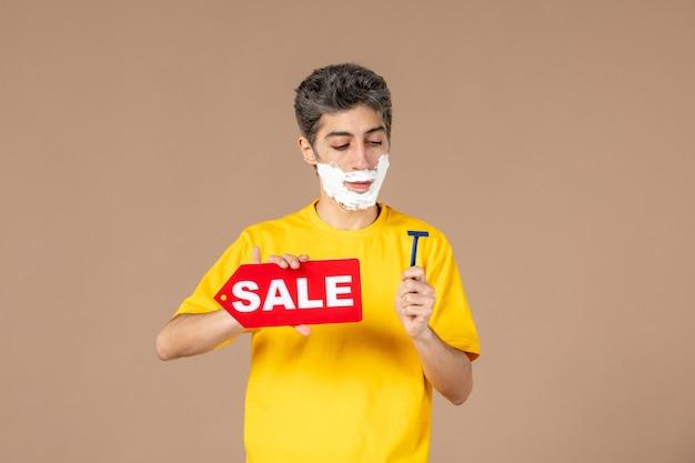 Vista frontale giovane maschio con il rasoio e la targhetta di vendita sulle sue mani su sfondo rosa