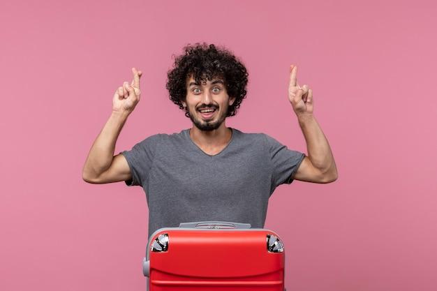 ピンクのスペースでhsiの指を交差する赤いバッグを持つ正面図若い男性