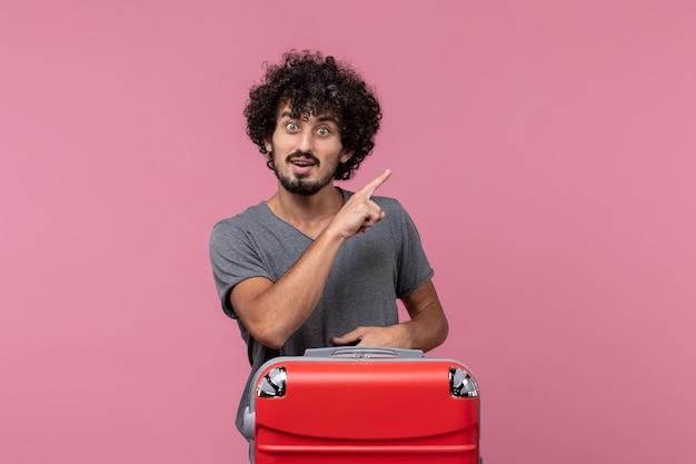 Giovane maschio di vista frontale con la borsa rossa che indica sullo spazio rosa
