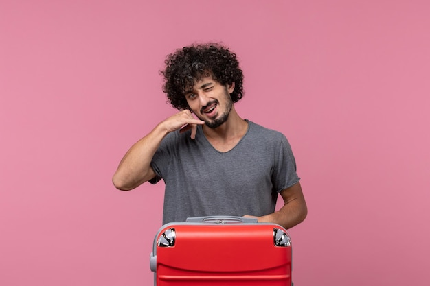 Front view young male with red bag posing on a pink space