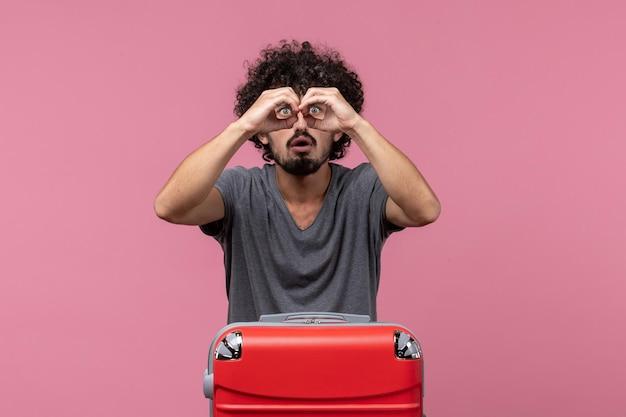 ピンクのスペースで旅行の準備をしている赤いバッグを持つ若い男性の正面図
