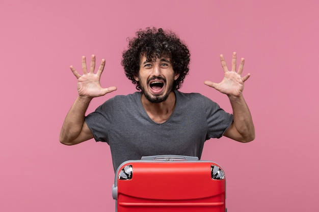 ピンクのスペースで怖い旅行の準備をしている赤いバッグを持つ若い男性の正面図