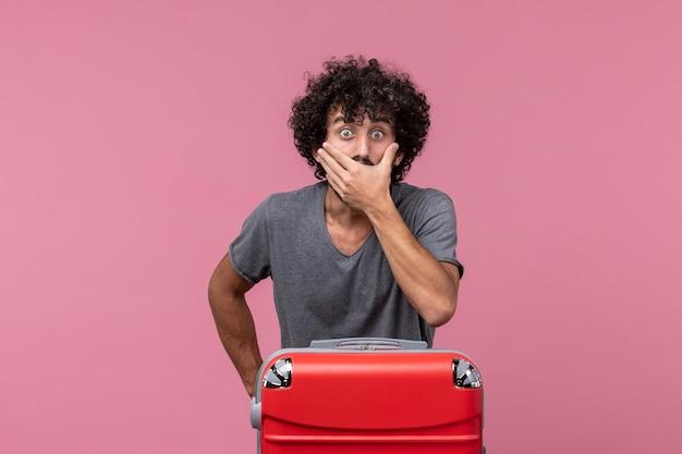 Vista frontale giovane maschio con borsa rossa che si prepara per il viaggio nello spazio rosa