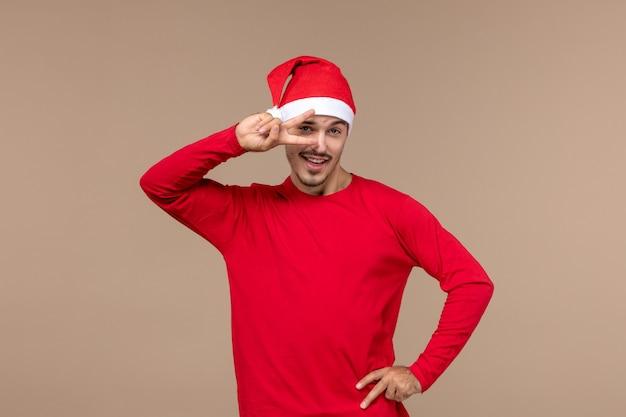 Вид спереди молодого мужчины с красной рождественской накидкой на коричневом фоне эмоции рождественского праздника