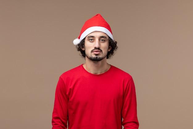 Вид спереди молодой самец с красной рождественской накидкой на коричневом фоне эмоции праздник рождество