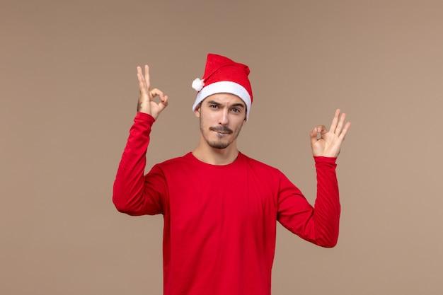 Вид спереди молодой мужчина с красной рождественской накидкой на коричневом фоне эмоции праздника мужчины