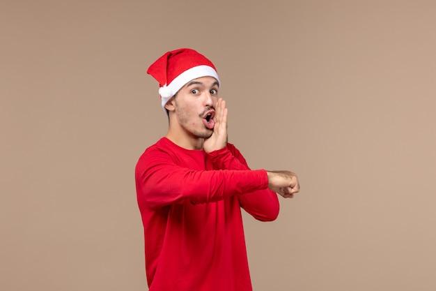 Вид спереди молодой мужчина с красной рождественской накидкой на коричневом фоне эмоции рождественский праздник