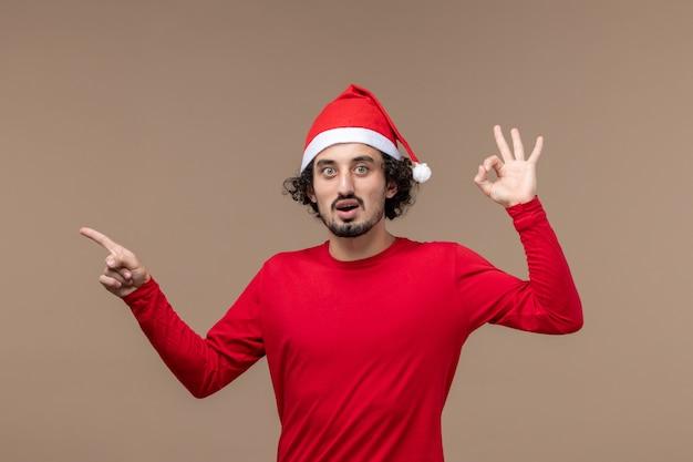 Вид спереди молодой мужчина с красной рождественской накидкой на коричневом фоне эмоции праздник рождество