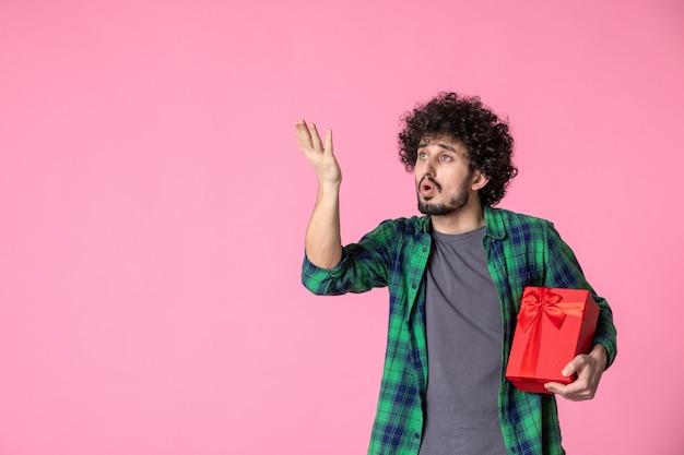 Vista frontale del giovane maschio con pacchetto rosso sulla parete rosa chiaro