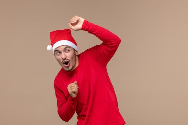 茶色の背景の男性の休日の感情に怖い表情で正面図若い男性