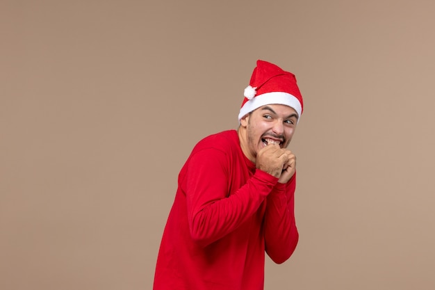 茶色の背景の休日の男性の感情に怖い表情を持つ若い男性の正面図