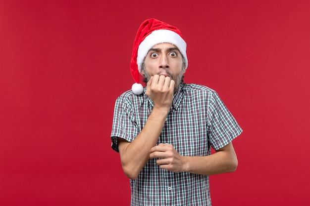 Giovane maschio di vista frontale con espressione spaventata su sfondo rosso