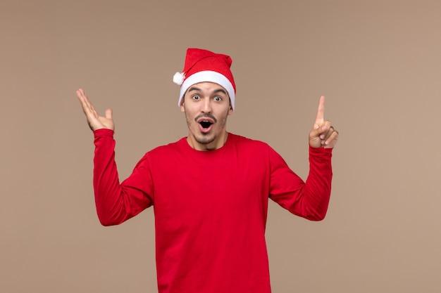 茶色の床のクリスマスの感情の休日にショックを受けた表情を持つ若い男性の正面図