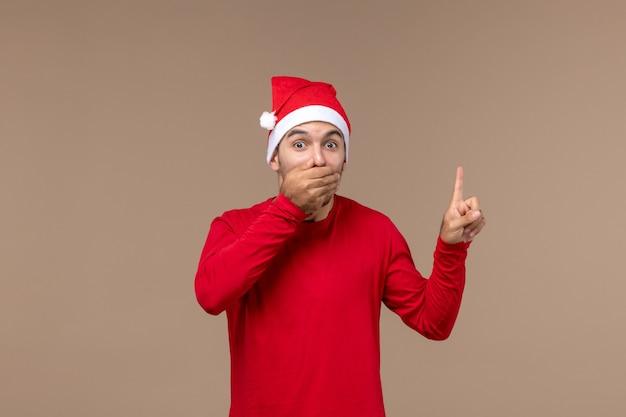 갈색 배경 크리스마스 감정 휴일 남성에 충격 된 얼굴로 전면보기 젊은 남성