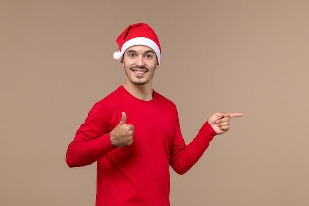 Вид спереди молодой мужчина с улыбающимся лицом на коричневом фоне эмоции праздник рождество