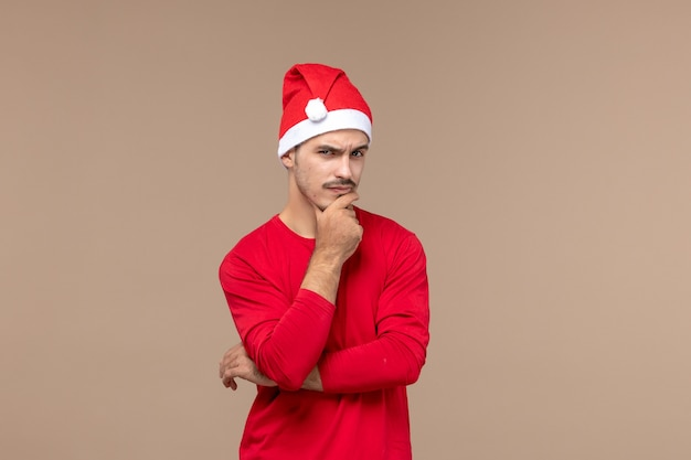 Front view young male with thinking expression on brown background male emotion holiday colors