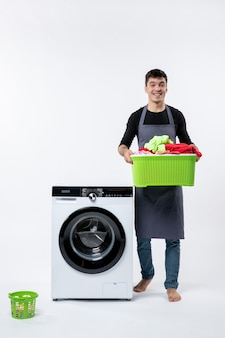 Front view of young male with washer and dirty clothes inside basket on white wall