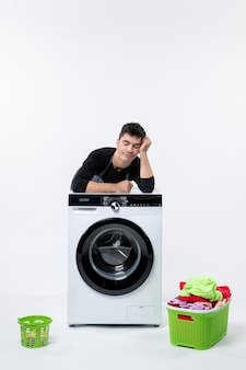 Front view of young male with washer and dirty clothes on a white wall