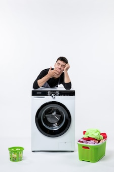 Front view of young male with washer and dirty clothes on white wall