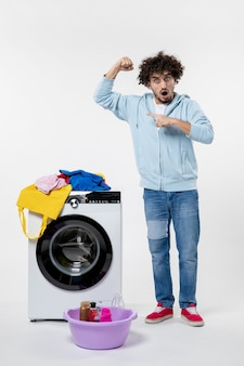 Front view of young male with washer flexing on white wall