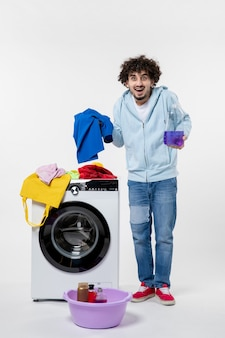 Front view of young male with washer holding liquid powder on white wall