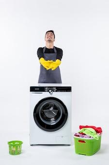 Vista frontale del giovane maschio con lavatrice e vestiti sporchi sul muro bianco